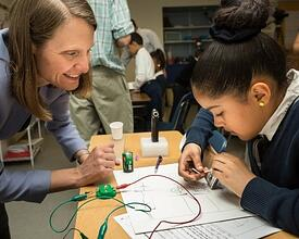 Young girl electrical engineering while adult helps