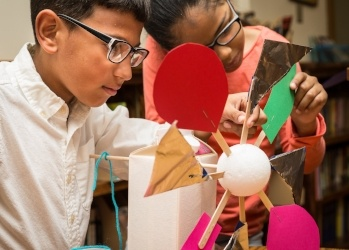 A young boy and girl engineer a model windmill