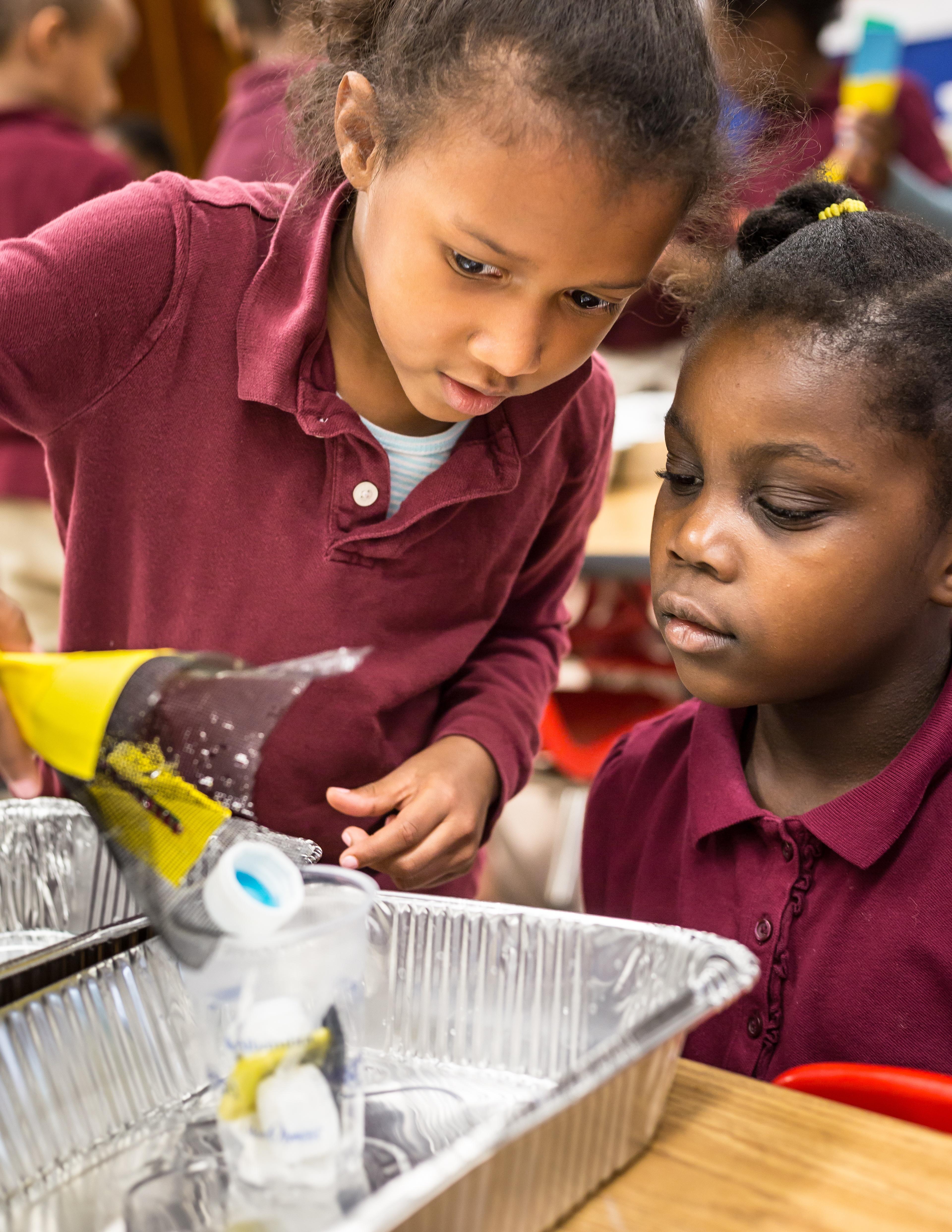 Two kindergarteners work together to engineer