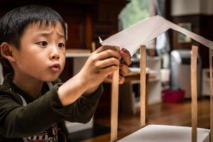 Asian kindergartner engineering a shelter