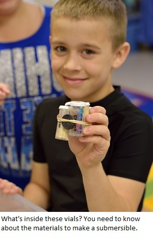 A boy holds a model submersible. Engineering is Elementary.