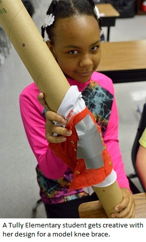 A Tully elementary student shows the creative knee brace she designed as part of a biomedical engineering challenge.