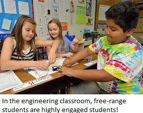 Three students work on completing a circuit and make a light bulb light up.